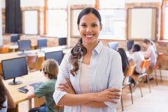 Ładny nauczyciel ono uśmiecha się przy kamerą przy plecy sala lekcyjna Obraz Stock