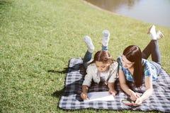 Ładny obrazek matki i córki lying on the beach na koc Dziewczyna rysuje na papieru prześcieradle z markierami Jej mama jest przyg zdjęcia royalty free