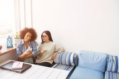 Ładny obrazek ucznie siedzi blisko do each inny na kanapie ja trzymają telefony w ich rękach dziewczyna amerykańska dziewczyna Zdjęcia Stock