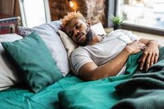 Ładny pokojowy mężczyzny dosypianie na jego łóżku obrazy royalty free