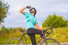 Ładny portret młoda żeńska cyklista atleta ma przerwę. Zdjęcia Stock