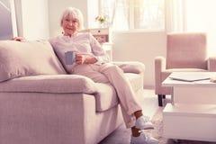 Ładny pozytywny emeryt jest ubranym lekkich modnych ubrania zdjęcia stock