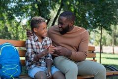 Ładny pozytywny mężczyzna daje małej teraźniejszości jego syn zdjęcia stock