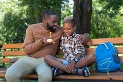 Ładny pozytywny mężczyzna daje tortowi jego syn obrazy stock