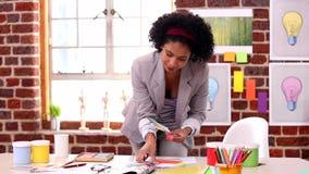 Ładny projektant pracuje przy jej biurkiem
