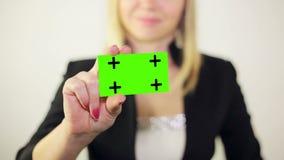 Ładny przyglądający bizneswoman pokazuje wizytówkę zdjęcie wideo