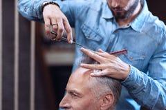 Ładny przystojny fryzjer męski trzyma jego klientów włosiani Zdjęcie Stock