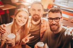 Ładny selfie dwa mężczyzna i jeden kobieta siedzi wpólnie bardzo zamkniętego i pozuje na kamerze Dziewczyna pokazuje symbol Obrazy Stock