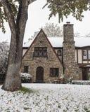 Ładny skała dom z łukowatymi drzwi i Tudor panelu stylowymi zaprowadzonymi szklanymi diamentowymi okno podczas opad śniegu obrazy stock