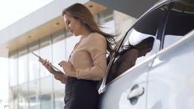 Ładny sprzedaż kierownik stoi blisko samochodu i działania na pastylce Bizneswoman zbiory