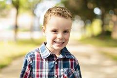Ładny uroczy chłopiec portret na zewnątrz pozyci zdjęcie stock