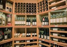 ładny zbliżenie widok różnorodny wino na drewnianym szelfowym ` s wśrodku wygodnego wino sklepu Fotografia Stock