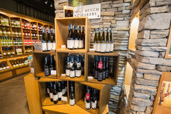 Ładny zbliżenie widok różnorodny wyśmienicie wino na drewnianym szelfowym ` s przeciw kamiennej ściany wina inside sklepowi Zdjęcia Royalty Free