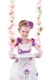 Ładnych małej dziewczynki blisko menchii kwiecista huśtawka odizolowywająca Obrazy Royalty Free