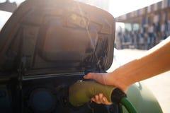 ładować elektryczny stacyjny pojazd Męska ręka ładuje elektrycznego samochód z władza kabla dostawą czopującą wewnątrz eco zdjęcia stock