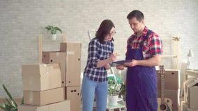 Ładowacz w mundurze i młodej kobiecie na tle pudełka dla ruszać się nowego dom zbiory