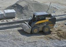Ładowacza małego buldożeru poruszający breakstone przy budowa terenem fotografia royalty free