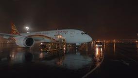 Ładowniczy ładunku zbiornik w samolot Hainan Airlines przy nocą zbiory