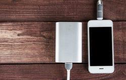 Ładuje smartphone z przenośną zewnętrznie baterią na drewnianym b Obraz Royalty Free