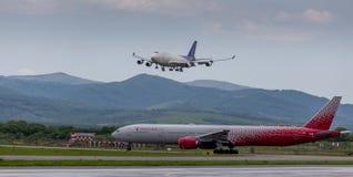 Ładunek samolotowy Aerotrans ładunku firma Boeing 747-412 ląduje Samolotowy Aerobus A330 Rossiya firma na lotnisku obraz royalty free