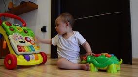 Ładunku elektrostatycznego strzał, śliczni siedem miesięcy starej chłopiec bawić się z edukacyjnymi zabawkami na podłogowym szczę zdjęcie wideo