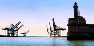 Ładunku port morski. Stara latarnia morska. Denni ładunków żurawie. Obrazy Royalty Free