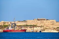 Ładunku statek cumował przy molem blisko fortu Ricasoli, Kalkar Fotografia Stock