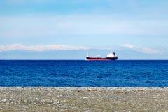 Ładunku statek w otwartym morzu przeciw tłu śnieg zakrywał góry obraz royalty free