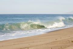 ?amaj?cy tubki fal? na piaskowatej pla?y z foamy backwash, otwiera rozleg?o?? ocean obraz stock