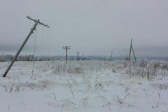 Łamanej fazy elektryczne linie energetyczne z hoarfrost na drewnianych elektrycznych słupach na wsi w zimie po burzy Obraz Royalty Free