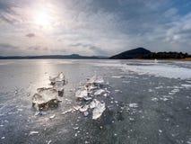 Łamani kawałki gęsty lód nad zamarzniętym jeziornym połyskiem w słońcu obraz stock