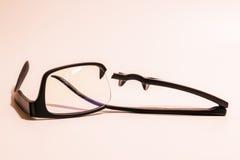 Łamani plastikowi Eyeglasses na barwionym tle Zdjęcia Royalty Free
