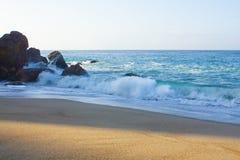 Łamanie fala na linii brzegowej z backwash, backspray, z piaskowatą plażą, przeciw falezie z skałami zdjęcie stock