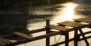 Łamany łamał bridżowy drewnianego z żółtym wschód słońca odbiciem na wodnym morzu w karimun jawie obraz royalty free