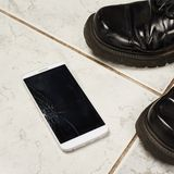 Łamany mądrze telefon nad płytkami Obrazy Royalty Free