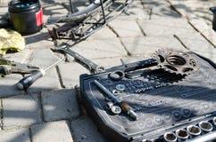 Łamany roweru, koła i axle zastępstwo, W tle narzędzia i części obraz royalty free