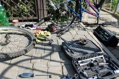 Łamany roweru, koła i axle zastępstwo, W tle narzędzia i części fotografia stock