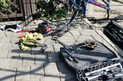 Łamany roweru, koła i axle zastępstwo, W tle narzędzia i części fotografia royalty free