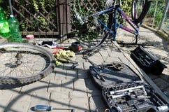 Łamany roweru, koła i axle zastępstwo, W tle narzędzia i części zdjęcie stock