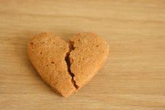 Łamany shortbread serce na drewnianym tle jako nieszczęśliwy miłości tło Obrazy Royalty Free