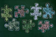 Łamigłówka kawałki różni kolory rysujący na chalkboard, jako fotografia royalty free