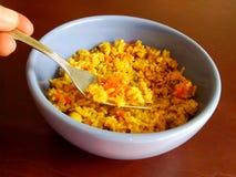 Łasowanie żółci ryż z błękitnego ceramicznego pucharu zdjęcie stock