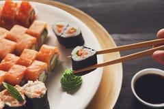 Łasowanie suszi rolki przy japońską karmową restauracją fotografia royalty free