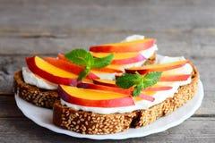 Łatwe kanapki z kremowym serem, świeżymi nektarynami i mennicą na talerzu na rocznika drewnianym stole, Fotografia Royalty Free