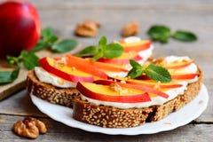 Łatwe kanapki z kremowym serem, świeżymi nektarynami, orzechami włoskimi i mennicą, na talerzu i na rocznika drewnianym stole Obraz Stock