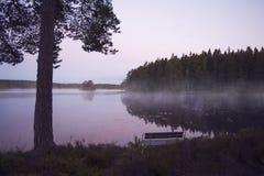 Ławka mglistym jeziorem w pięknym wschodzie słońca Zdjęcia Stock