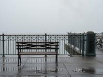 Ławka przegapia mgłowej zatoki na deszczowym dniu obraz royalty free