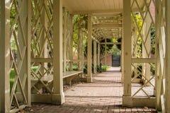 Ławka Seat pod Drewnianym Archway na Ceglanej ścieżce Zdjęcia Stock