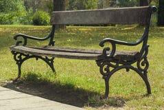 Ławka w parku z zieloną trawą i drewnami Obrazy Stock