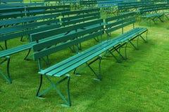 ławki opróżniają trawy zieleni plenerowych rzędy Obrazy Stock